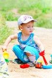与玩具的小儿童游戏在沙子 免版税图库摄影