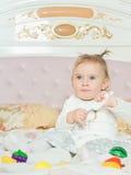 与玩具的小白种人儿童女孩戏剧在床上在家 免版税库存图片