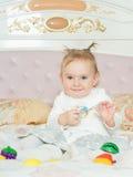 与玩具的小白种人儿童女孩戏剧在床上在家 免版税库存照片