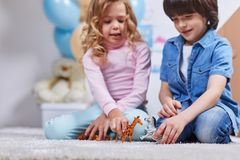 与玩具的快乐的儿童游戏在地毯 免版税库存照片