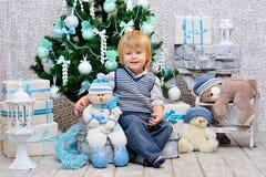 与玩具的愉快的孩子由圣诞树 免版税库存图片