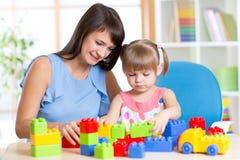 与玩具的母亲和孩子戏剧在家 库存照片
