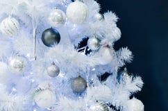 与玩具的白色圣诞节快乐树在黑墙壁上 库存照片