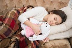 与玩具的睡眠 女孩喜欢平衡与喜爱的玩具的时间 孩子位置床和拥抱兔宝宝玩具长沙发枕头毯子背景 库存照片