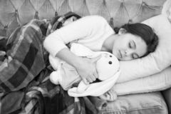 与玩具的睡眠 女孩喜欢平衡与喜爱的玩具的时间 孩子位置床和拥抱兔宝宝玩具长沙发枕头毯子背景 免版税图库摄影