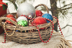 与玩具的篮子在一棵圣诞树附近的一个多雪的森林里与稀土 免版税图库摄影