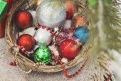 与玩具的篮子在一棵圣诞树附近的一个多雪的森林里与稀土 免版税库存图片