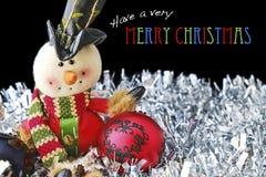 与玩具雪人和中看不中用的物品的圣诞快乐在闪亮金属片 免版税图库摄影