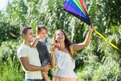 与玩具风筝的家庭在公园 免版税库存图片