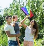 与玩具风筝的家庭在公园 免版税图库摄影