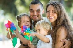 与玩具风车的家庭在公园 免版税库存照片