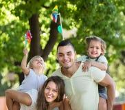 与玩具风车的家庭在公园 库存图片