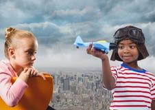 与玩具飞机的孩子在城市 免版税库存图片