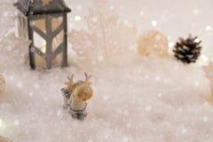 与玩具鹿的新年卡片在冬天背景的一个神仙的森林里与雪和光 库存图片