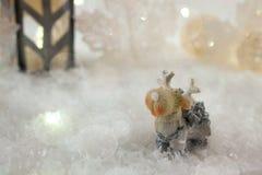 与玩具鹿的新年卡片在冬天背景的一个神仙的森林里与雪和光 图库摄影