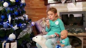 与玩具,获得愉快的婴孩的儿童游戏吃蛋糕macaron,逗人喜爱的小女孩哺养的玩具小狗的乐趣圣诞节曲奇饼 股票录像