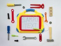 与玩具,锁匠工具,委员会信件,顶视图的背景 免版税库存照片
