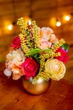 与玫瑰、八仙花属、连翘属植物和绿叶的花的布置在桌上的一个花瓶 库存图片
