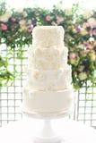 4与玫瑰华饰点缀和花卉背景的排白色婚宴喜饼 免版税库存图片