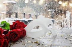 与玫瑰和化妆舞会白色面具美丽的花束的情人节浪漫背景在木桌上 免版税库存照片
