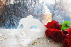 与玫瑰和化妆舞会白色面具美丽的花束的浪漫图象在木桌上 库存照片