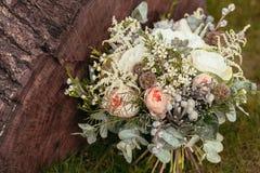 与玫瑰和多汁植物的土气婚礼花束在绿草 免版税库存图片