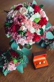与玫瑰和康乃馨的五颜六色的婚礼花束在女傧相钮扣眼上插的花旁边的有圆环的桌和箱子上 免版税库存图片