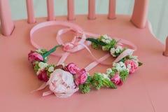 与玫瑰和牡丹的美丽的花圈在桃红色椅子 库存图片