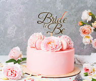 与玫瑰和蛋白杏仁饼干的桃红色婚宴喜饼与是轻便短大衣的新娘 顶视图,平的位置 免版税库存图片