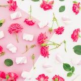 与玫瑰和蛋白软糖的桃红色淡色背景 平的位置 顶视图 免版税图库摄影