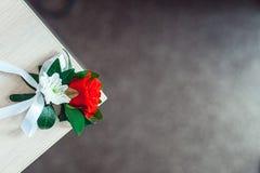 与玫瑰的一点婚礼钮扣眼上插的花与白色丝带 库存图片