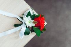 与玫瑰的一点婚礼钮扣眼上插的花与白色丝带 免版税库存图片