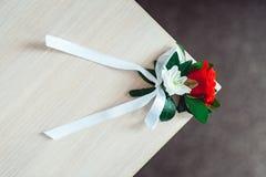 与玫瑰的一点婚礼钮扣眼上插的花与白色丝带 图库摄影