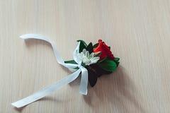 与玫瑰的一点婚礼钮扣眼上插的花与白色丝带 库存照片