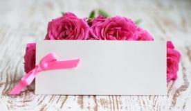 与玫瑰的卡片在桌上 库存图片