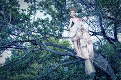 与玫瑰的夫人佩带的空白礼服在木头 免版税库存图片