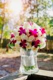 与玫瑰的婚礼花束在一个长木凳 免版税图库摄影