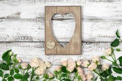 与玫瑰的木心脏形状框架 免版税库存图片