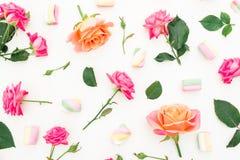与玫瑰的样式开花,芽、叶子和蛋白软糖糖果在白色背景 平的位置,顶视图 免版税库存照片