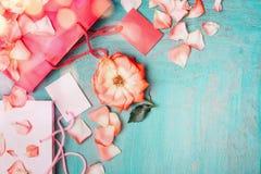 与玫瑰的桃红色纸购物袋和在蓝色绿松石背景,顶视图的空白的标记 免版税库存图片