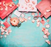 与玫瑰的桃红色苍白纸购物袋和在蓝色绿松石背景,顶视图的空白的标记 库存图片