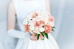 与玫瑰的甜婚姻的花束在新娘的手上 免版税库存照片