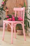 与玫瑰美妙的花束的桃红色凳子  免版税图库摄影
