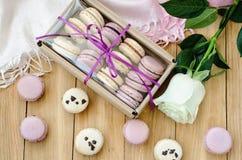 与玫瑰色和礼物盒的淡紫色蛋白杏仁饼干 顶视图 免版税库存图片