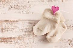 与玫瑰色心脏的被编织的婴孩袜子木表面上 库存照片