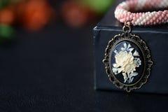 与玫瑰色有浮雕的贝壳的短的串珠的窒息物在黑暗的背景 库存照片