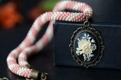 与玫瑰色有浮雕的贝壳的短的串珠的窒息物在黑暗的背景 库存图片