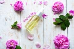 与玫瑰色精华油的有机化妆用品在白色木背景温泉治疗 温泉按摩 免版税库存照片