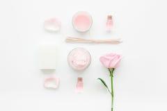 与玫瑰色花和化妆用品的温泉集合在白色书桌背景顶视图的身体的 免版税图库摄影