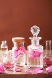 与玫瑰色花和烧瓶的香料厂和芳香疗法集合 库存照片